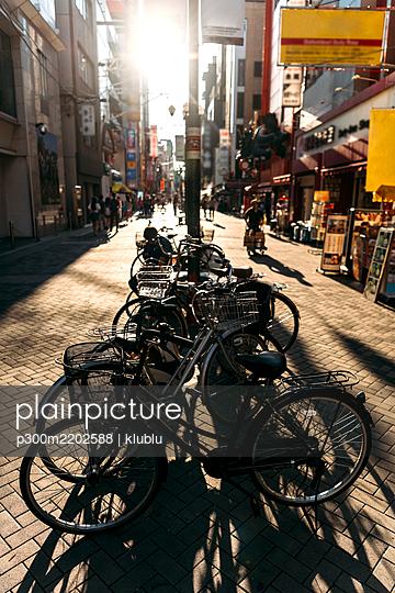 Japan, Osaka Prefecture, Osaka, Sun setting over bicycles parked on Dotonbori street - p300m2202588 by klublu