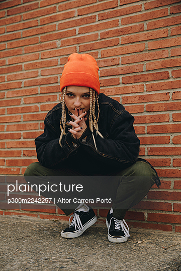 Beautiful woman wearing knit hat and jacket crouching while posing on road against brick wall - p300m2242257 by Aitor Carrera Porté