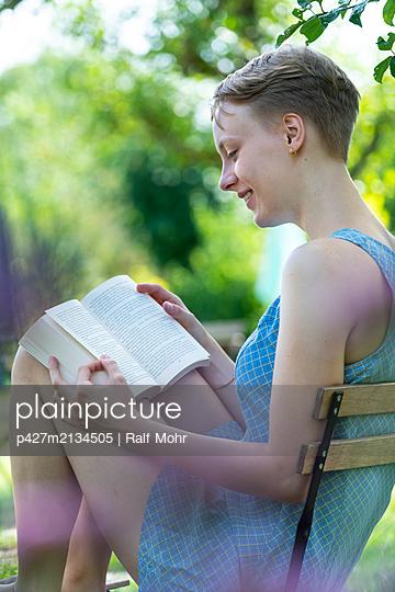 Junge Frau liest ein Buch im Garten - p427m2134505 von Ralf Mohr