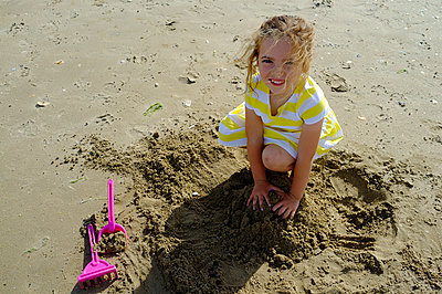 A small girl playing with sand in a beach - p1096m1464842 by Rajkumar Singh