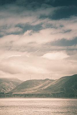 Windkraftanlagen auf einer Hügelkette am See - p1255m1574976 von Kati Kalkamo