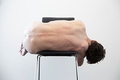 Naked young man on a chair - p1650m2272218 by Hanna Sachau