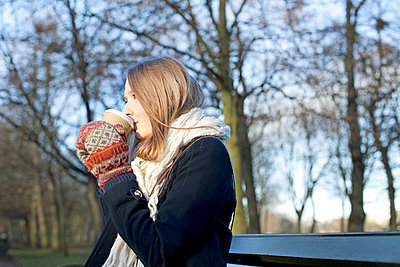 Woman having coffee on park bench - p924m807250f by Sydney Bourne