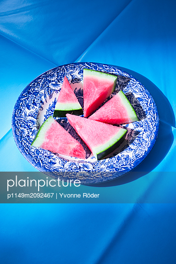 Pieces of melon on blue plate - p1149m2092467 by Yvonne Röder