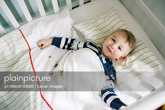 Little toddler boy in his crib not wanting to nap. - p1166m2159560 by Cavan Images