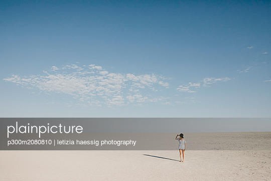 Woman with black hat, walking in the desert - p300m2080810 by letizia haessig photography