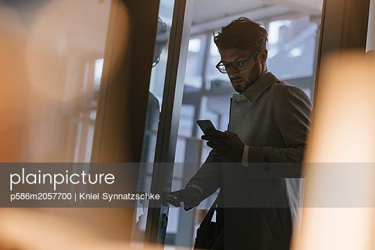 Man in office using smartphone - p586m2057700 by Kniel Synnatzschke