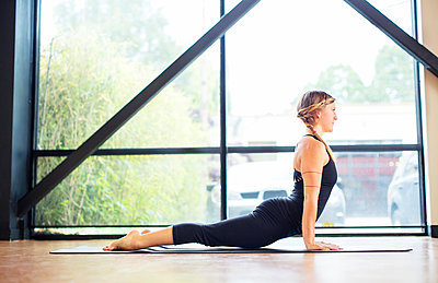 Side view of woman practicing cobra pose by window in yoga class - p1166m1209748 by Cavan Images