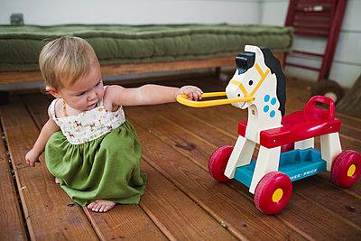 Kleines Mädchen mit seinem Schaukelpferd - p1361m1477228 von Suzanne Gipson