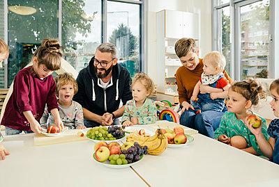 Group of children and teachers preparing fruit in kindergarten - p300m1537447 by Mareen Fischinger