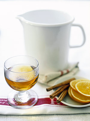 Glass of tea with cinnamon sticks and slices of orange. - p349m2167689 by Polly Wreford