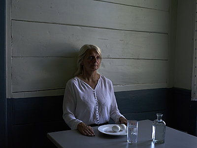 Senior woman sits by the table - p945m1163013 by aurelia frey