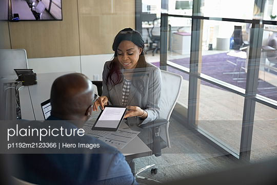 Businesswoman with digital tablet talking to client - p1192m2123366 by Hero Images