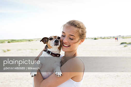 Young woman on beach playing with dog - p341m1480689 by Mikesch