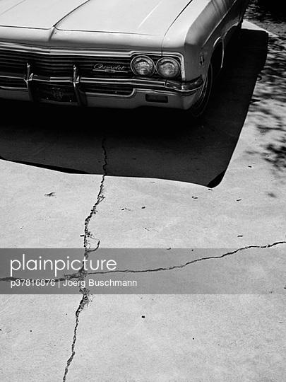Car on cracked pavement - p37816876 by Joerg Buschmann