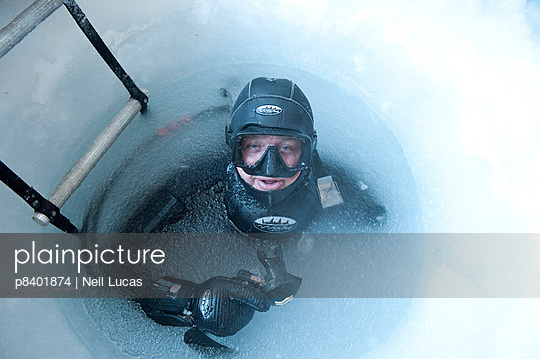 Camerman Doug Allan at frozen water surface of drilled ice hole - p8401874 by NEIL LUCAS
