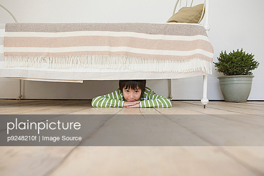Boy hiding under a bed - p9248210f by Image Source