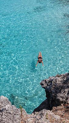 Frau schwimmt im türkisblauen Meer - p045m1572920 von Jasmin Sander