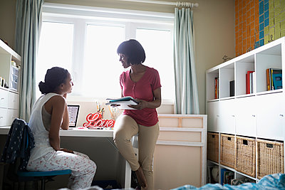 Mother helping teenage daughter with homework at desk in bedroom - p1192m2000341 by Hero Images