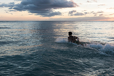Male surfer surfing with surfboard in the sea at dusk - p1315m2014160 by Wavebreak