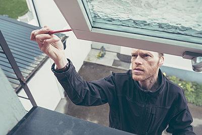 Man repairing window  - p1687m2284292 by Katja Kircher