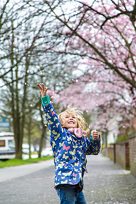 Little girl throwing cherry blossoms in the air - p300m1023129f by Jana Fernow