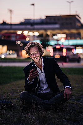 Smiling businessman sitting on meadow at dusk with cell phone and earphones - p300m1228423 by Kniel Synnatzschke
