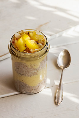 Glass of chia pudding with mango smoothie garnished with kiwi and coconut flakes - p300m1581042 by Eva Gruendemann