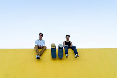 Two young men with skateboards sitting on a high yellow wall - p300m2028701 von VITTA GALLERY