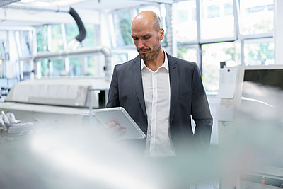Balding businessman looking at digital tablet while standing at bright factory - p300m2221243 by Robijn Page