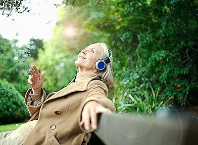 Senior woman (55-65) sitting on bench, listening to music through headphones, London, United Kingdom - p300m2287252 von LOUIS CHRISTIAN