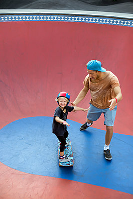 Father supporting son on skateboard in skate park, Canggu, Bali, Indonesia - p343m1543783 by Konstantin Trubavin