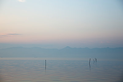 Scenic view of lake against sky during sunset - p1166m2000838 by Cavan Images