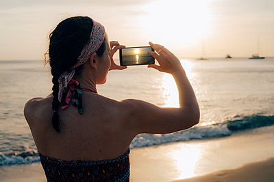 Thailand, Koh Lanta, woman on the beach taking photo with cell phone at sunset - p300m2004663 by Gemma Ferrando