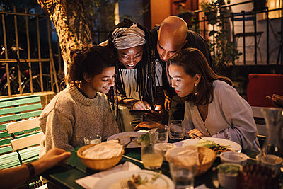 Happy young woman showing smart phone to friends at table during dinner party - p426m2046184 by Maskot