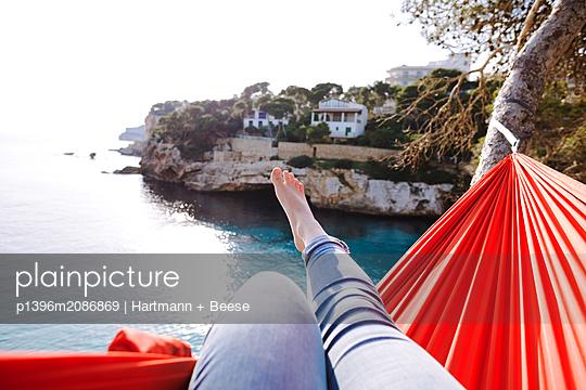Frau liegt in Hängematte mit Blick auf das Meer - p1396m2086869 von Hartmann + Beese