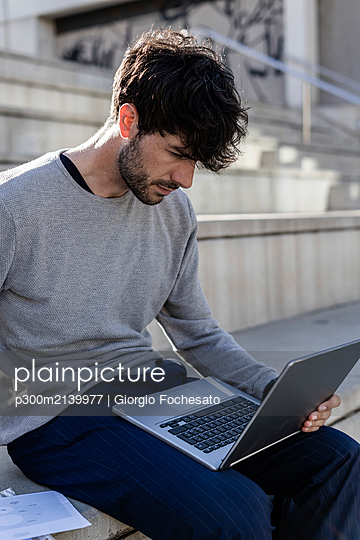 Man sitting on outdoor stairs using laptop - p300m2139977 by Giorgio Fochesato
