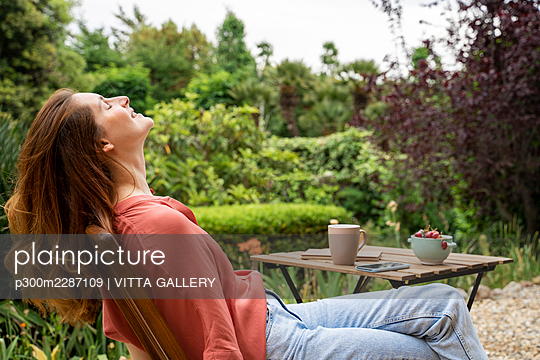 Barcelona, Spain. Young woman relaxing outdoors in garden. Relax, garden, work from home, stay at home, home, work, home office, relax, chill, free time, leisure - p300m2287109 von VITTA GALLERY