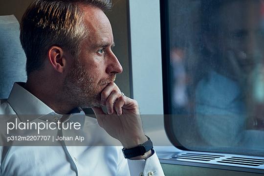 Man looking through train window - p312m2207707 by Johan Alp