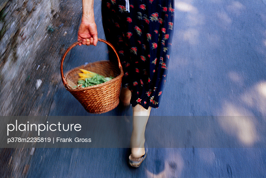 Woman carrying basket - p378m2235819 by Frank Gross