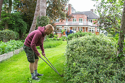 Man with pruning shears in garden - p1026m1164175 by Patrick Frost
