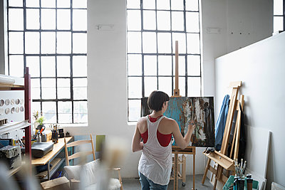 Female painter painting at canvas on easel in art studio - p1192m1490237 by Hero Images