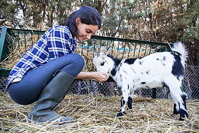 Woman feeding a goat on a farm - p300m1192372 by Andrés Benitez