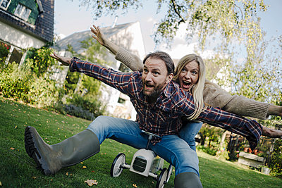 Laughing couple, pretending to fly on a toy car in the garden - p300m2166718 by Kniel Synnatzschke