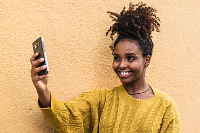 Smiling young woman taking selfie through mobile phone by yellow wall - p300m2243301 by NOVELLIMAGE