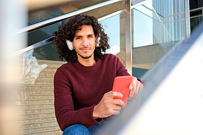 Caucasian young man with headphones holding mobile phone at structure - p300m2273614 by Antonio Ovejero Diaz