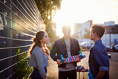 Young male skateboarders chatting on sunlit street - p429m1224335 by Matt Lincoln