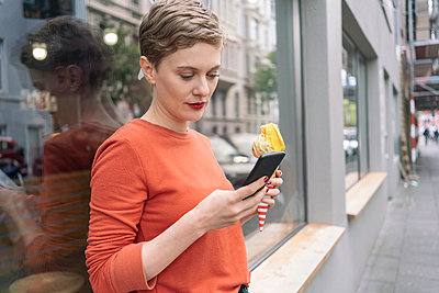Woman holding ice cream and using smartphone in front of shop, Cologne, Nordrhein-Westfalen, Germany - p429m2077842 by Tamboly