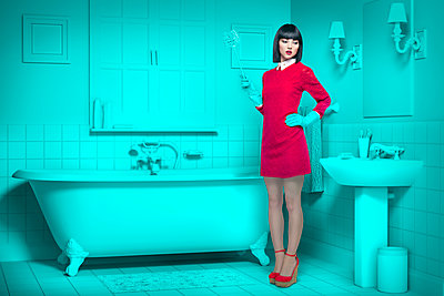 Caucasian woman in teal old-fashioned bathroom holding cleaning brush - p555m1304583 by Chris Clor