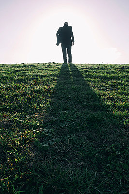 Silhouette of man walking over grass field - p597m2026528 by Tim Robinson